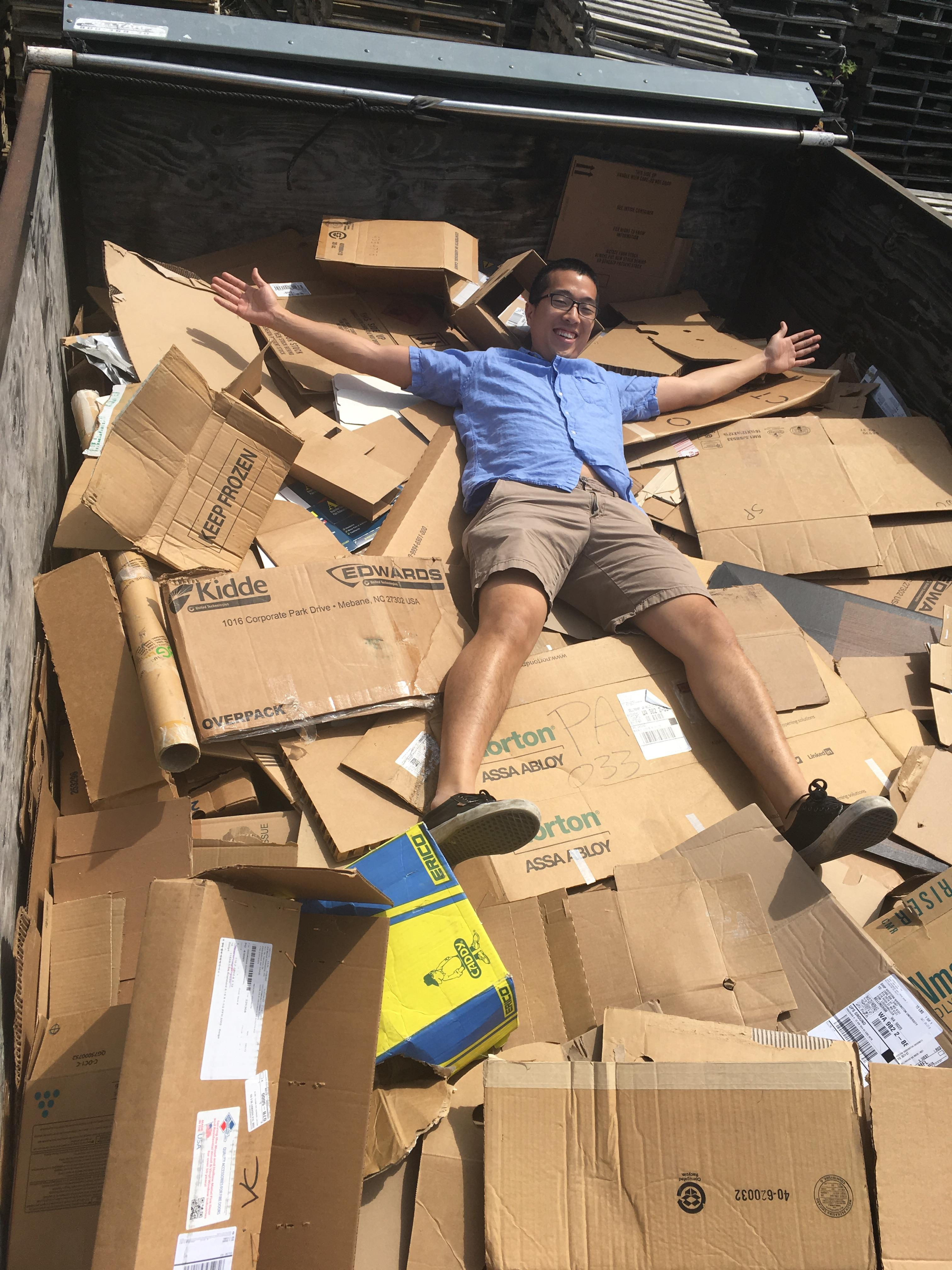 Kenji laying in the back of our full cardboard truck