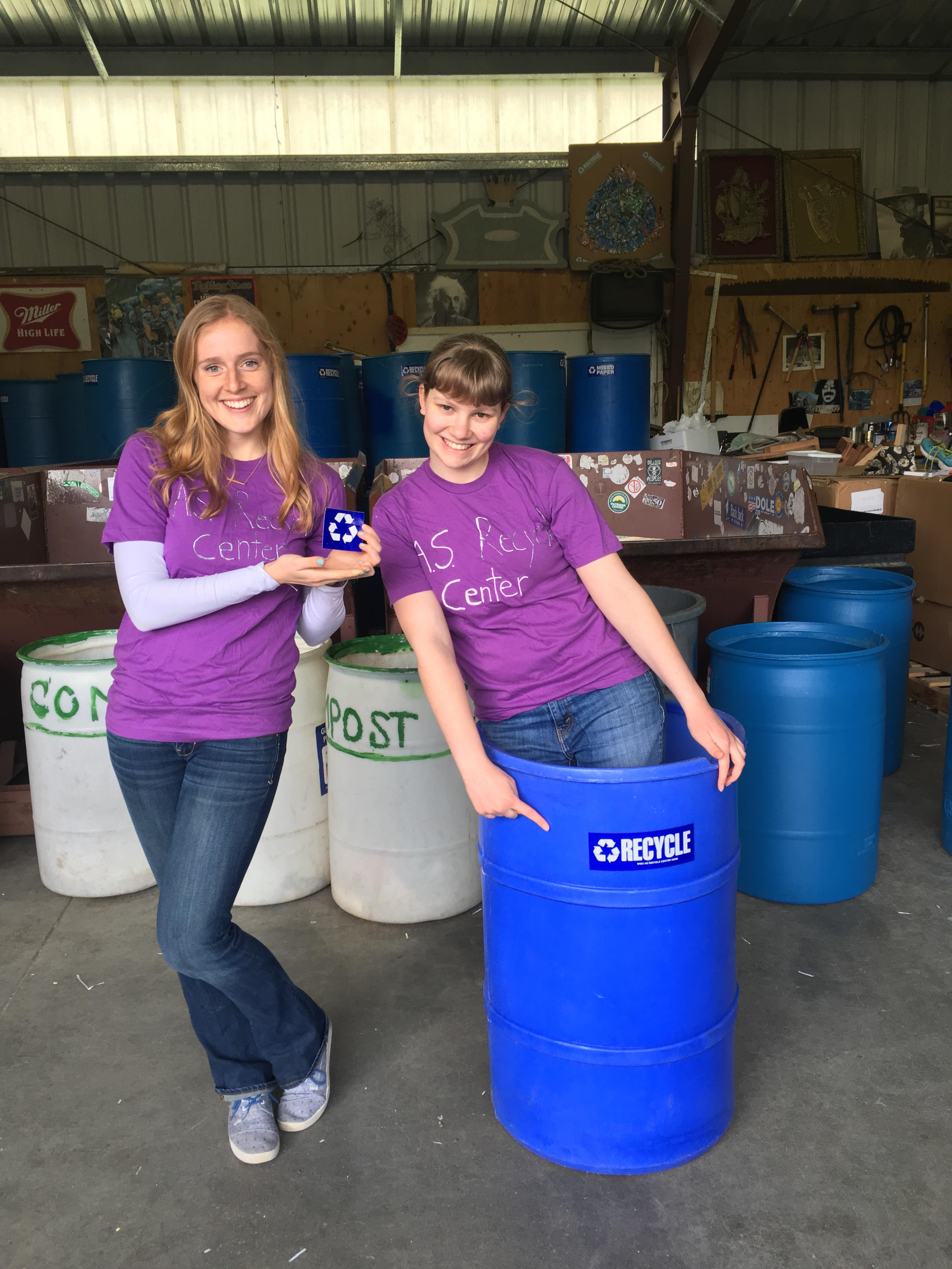 Recycling cuties behind two blue recycling barrels